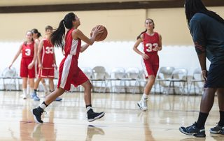 Girls Basketball team playing on a highly reflective floor surface